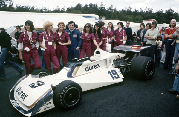 Alan Jones poses with his Surtees TS19 Ford and Durex models.
