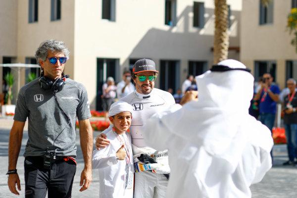 Yas Marina Circuit, Abu Dhabi, United Arab Emirates. Saturday 25 November 2017. Fernando Alonso, McLaren, poses with a young fan. World Copyright: Steven Tee/LAT Images  ref: Digital Image _R3I2915