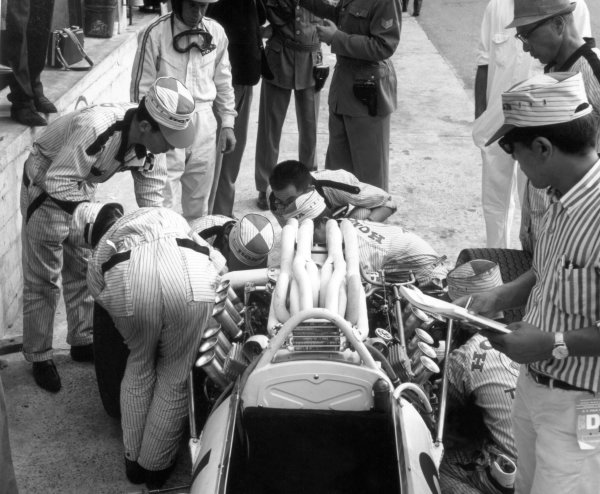 1966 Italian Grand Prix.Monza, Italy. 4 September 1966.Richie Ginther, Honda RA273, retired, watches mechanics work on his car, portrait, helmet.World Copyright: LAT PhotographicRef: 36208A