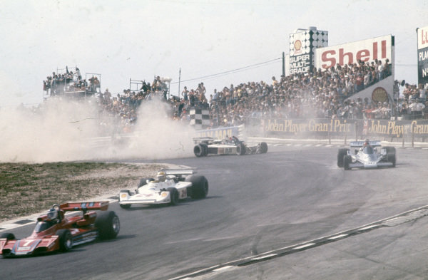 Guy Edwards, Hesketh 308D Ford gets back on track behind Emerson Fittipaldi, Fittipaldi FD04 Ford after spinning.
