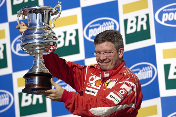 Ross Brawn proudly presents the constructors' trophy on the podium.