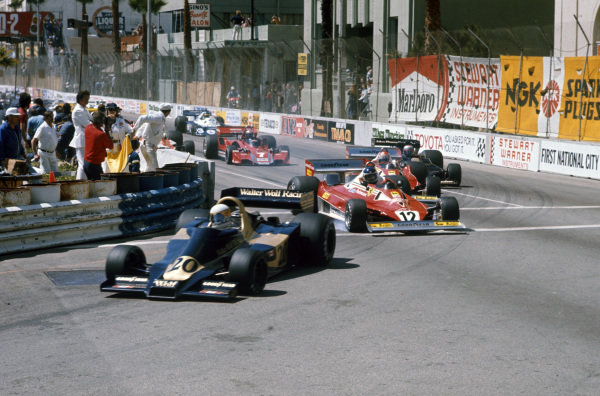 Jody Scheckter, Wolf WR1 Ford leads Carlos Reutemann, Ferrari 312T2 who locks up ahead of Niki Lauda, Ferrari 312T2 at the start.