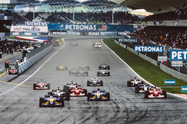 Fernando Alonso, Renault R23, leads Jarno Trulli, Renault R23, David Coulthard, McLaren MP4-17D Mercedes, and Michael Schumacher, Ferrari F2002, at the start.