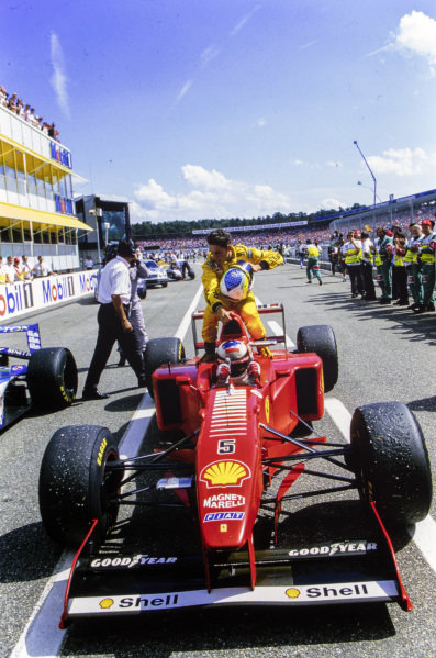 Michael Schumacher, Ferrari F310B, gives Giancarlo Fisichella a lift back to the pits at the end of the race.