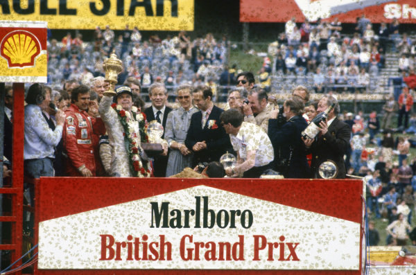 Alan Jones, 1st position, raises his trophy in front of Carlos Reutemann, third position, on the podium.