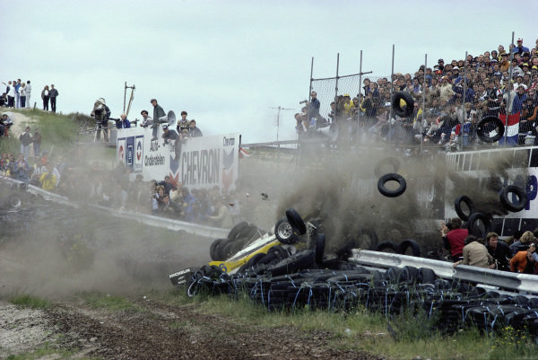 Rene Arnoux, Renault RE30B, crashes into a tyre barrier sending loose tyres flying towards photographers, after a wheel (far left of frame) came off his car.