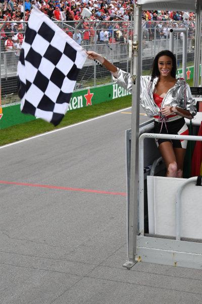 Winnnie Harlow (CDN) waves the chequered flag .