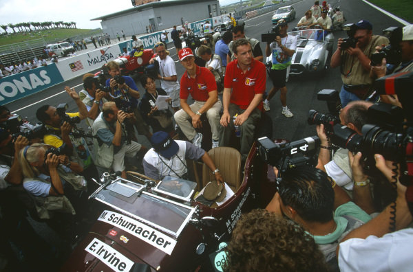 Sepang, Kuala Lumpur, Malaysia. 15-17 October 1999. Ferrari teammates Michael Schumacher and Eddie Irvine surrounded by photographers in the pre-race drivers parade. Atmosphere. Ref: 99MAL18. World Copyright - LAT Photographic