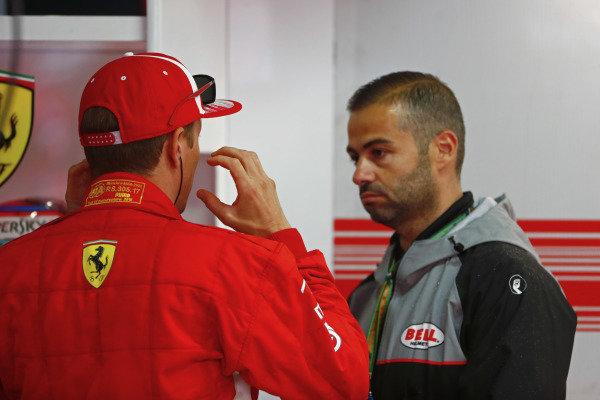 Kimi Raikkonen, Ferrari, talks to a Bell helmets employee.