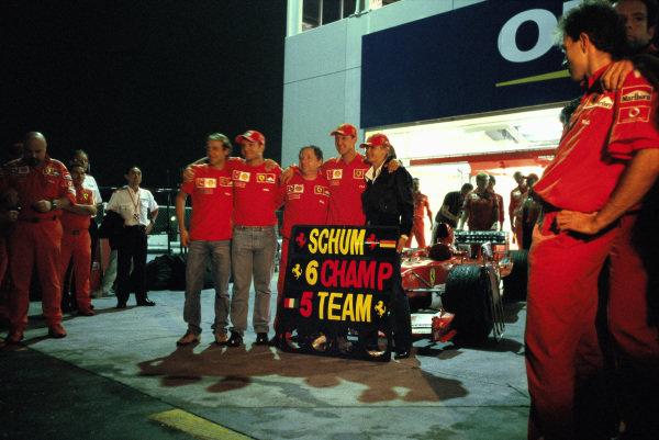 Michael Schumacher celebrates his sixth world championship with Ferrari test driver Luca Badoer, Rubens Barrichello, Jean Todt and wife Corinna.