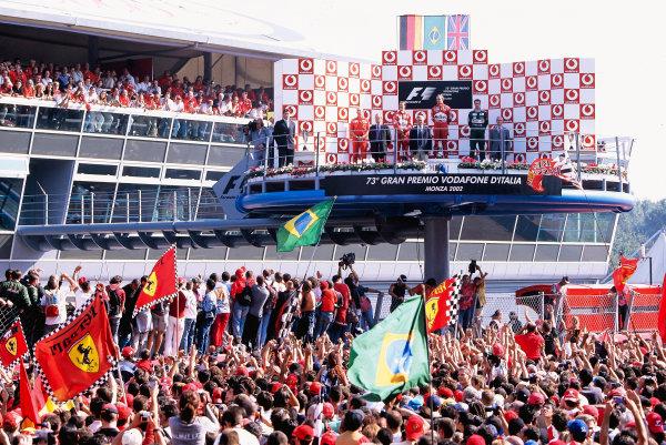 2002 Italian Grand PrixMonza, Italy. 14th - 16th September 2002Rubens Barrichello, Ferrari F2002, Michael Schumacher, Ferrari F2002, Eddie Irvine, Jaguar Cosworth R3, on the podium.World Copyright - LAT Photographicref: 35mm Transparency 02_ITA_34