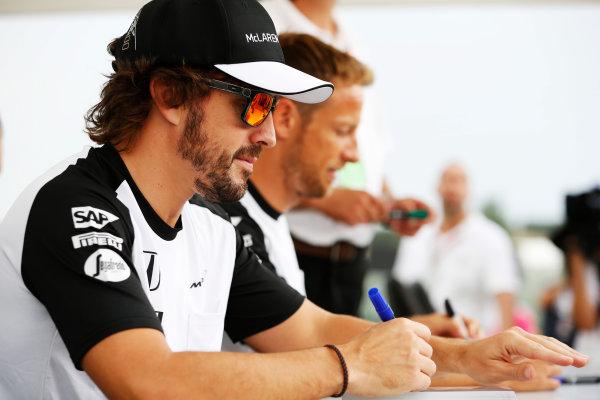 Hungaroring, Budapest, Hungary. Thursday 23 July 2015. Fernando Alonso, McLaren, and Jenson Button, McLaren, sign autographs for fans. World Copyright: Charles Coates/LAT Photographic ref: Digital Image _J5R0891