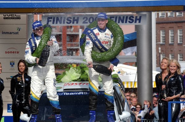 Markko Martin (EST), right, and co-driver Michael Park (GBR), Ford, celebrate their victory on the podium. FIA World Rally Championship, Rd9, Neste Rally Finland, Jyvaskyla, Finland, Day 3, 10 August 2003. DIGITAL IMAGE