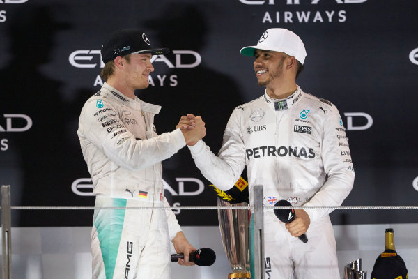 Yas Marina Circuit, Abu Dhabi, United Arab Emirates. Sunday 27 November 2016. New World Champion Nico Rosberg, Mercedes AMG, 2nd Position, and outgoing champion Lewis Hamilton, Mercedes AMG, 1st Position, congratulate each other on the podium. World Copyright: Steve Etherington/LAT Photographic ref: Digital Image SNE11156