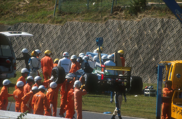 1991 Japanese Grand Prix.Suzuka, Japan.18-20 October 1991.Marshals remove the Lola L91 Ford as medical staff attend to Eric Bernard after his bad accident at the end of Friday morning's free practice session. His car hit the wall with such force that he broke his left leg and cracked his knee-cap in the impact.Ref-91 JAP 19.World Copyright - LAT Photographic