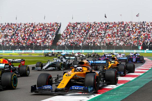 Carlos Sainz Jr., McLaren MCL34, leads Max Verstappen, Red Bull Racing RB15, Lando Norris, McLaren MCL34, Valtteri Bottas, Mercedes AMG W10, Daniil Kvyat, Toro Rosso STR14, and the remainder of the field at the start