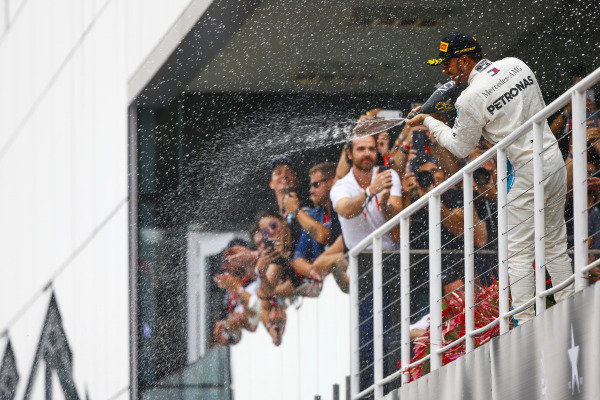 Lewis Hamilton, Mercedes AMG F1, celebrates victory on the podium. by spraying champagne.