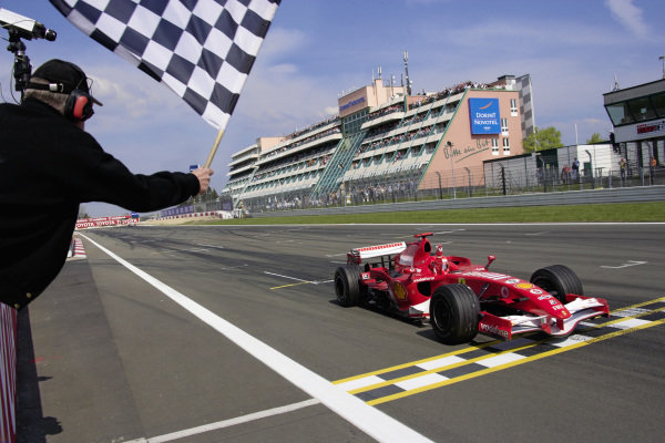 Michael Schumacher, Ferrari 248 F1 takes the chequered flag for victory.