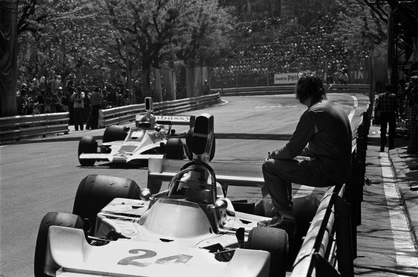 Montjuich Park, Spain. 27 April 1975. James Hunt (Hesketh 308-Ford), retired, watches Rolf Stommelen (Hill GH1-Ford), retired, action.  World Copyright: LAT Photographic Ref: B/W Print
