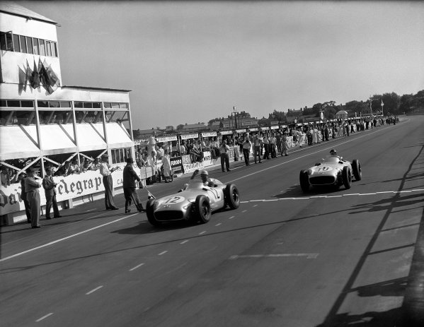 Aintree, England. 14 - 16 July 1955.Stirling Moss leads Juan Manuel Fangio (both Mercedes-Benz W196) in 1st and 2nd positions respectively at the finish, action. World Copyright: LAT Photographic.Ref:  Autocar Glass Plate C44144.