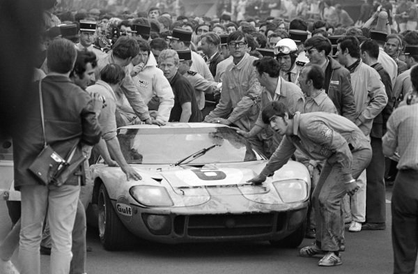 The Jacky Ickx / Jackie Oliver, John Wyer Automotive Engineering Ltd, Ford GT40 drives into Parc Ferme as their mechanics push the car through the crowd.