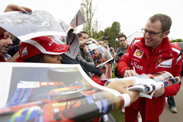 Stefano Domenicali signs autographs for fans.