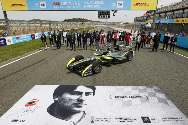 The drivers and Formula E personnel line up on the grid with the Gen1 car to pay tribute to Adrian Campos