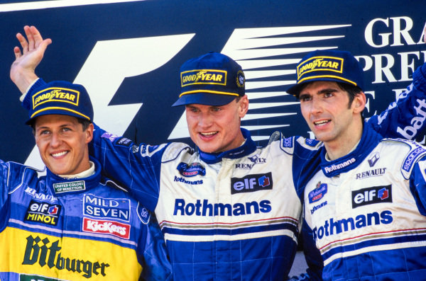 Michael Schumacher, 2nd position, David Coulthard, 1st position, and Damon Hill, 3rd position, celebrate on the podium.