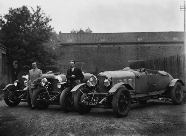 "The Bentley 4-1/2 litre team cars for the 1929 Le Mans race (the lead lined ballast tubes across the tops of the dumb-irons, and the central headlights are the give away). Henry ""Tim"" Birkin on the left and Frank Clement leaning on the wing of the prototype 41/2 in the middle. No hoods had to be erected that year so the newer cars did not have the ""traditional"" squared-off tails which had been used in previous races. The photo could be at Barnato's house ""Ardenrun"" near Lingfield, Surrey, where the team used to stop for lunch before catching the ferry from Newhaven, portrait. 