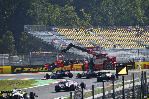 Marshals remove the car of Max Verstappen, Red Bull Racing RB16, as Lewis Hamilton, Mercedes F1 W11 EQ Performance, leads the field past the scene