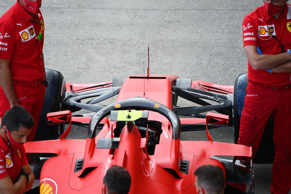 Mechanics stand next to the Charles Leclerc Ferrari SF1000