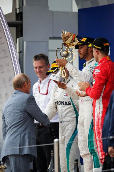 Valtteri Bottas, Mercedes AMG F1, 2nd position, and Sebastian Vettel, Ferrari, 3rd position, applaud as Lewis Hamilton, Mercedes AMG F1, 1st position, receives his trophy from Vladimir Putin, President of Russia
