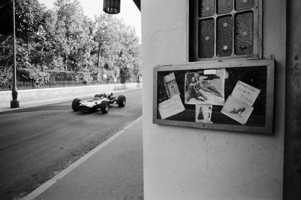 Lucien Bianchi, Cooper T86B BRM, passes the entrance to a strip tease bar.