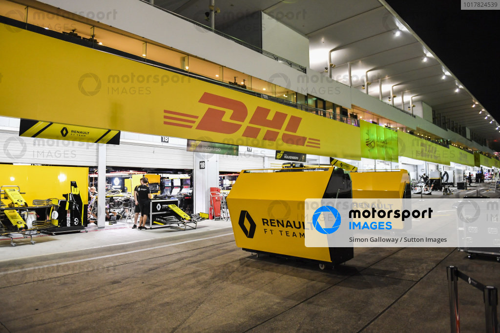 Teams clear equipment in the pit lane in anticipation of typhoon storms on Saturday