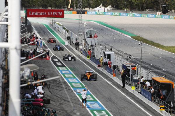 Lando Norris, McLaren MCL35M, Nicholas Latifi, Williams FW43B, and Esteban Ocon, Alpine A521, in the pit lane