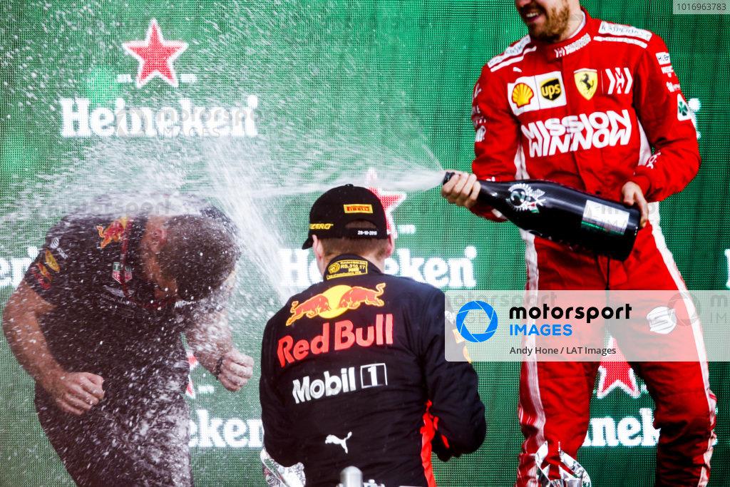 Max Verstappen, Red Bull Racing, 1st position, and Sebastian Vettel, Ferrari, 2nd position, spray Champagne on the podium