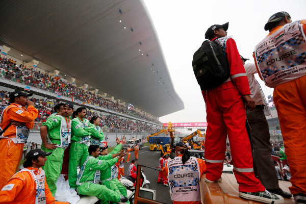 2012 Indian Grand Prix - Sunday Buddh International Circuit, New Delhi, India. 28th October 2012. Marshals and spectators gain the best viewing advantages they can for the podium celebrations. World Copyright:Charles Coates/LAT Photographic ref: Digital Image _N7T6023