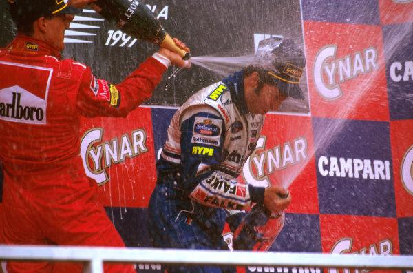 Imola, San Marino.25-27 APRIL 1997.Heinz-Harald Frentzen (Williams Renault) celebrates taking his maiden F1 win on the podium, whilst being sprayed by Michael Schumacher (Ferrari) 2nd.Ref-97 SM 10.World  Copyright - LAT Photographic