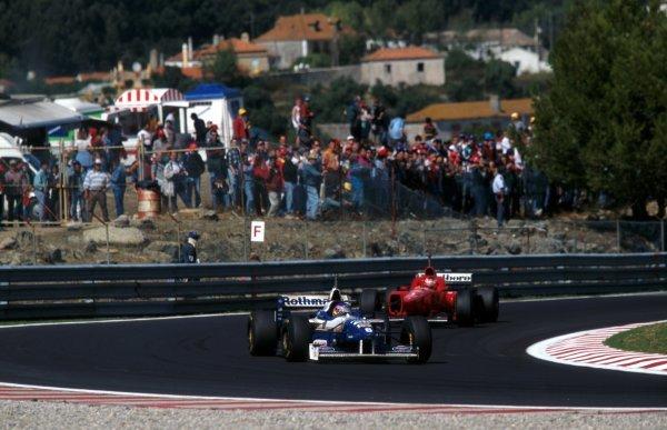 Race winner Jacques Villeneuve (CDN) Williams FW18 leads third placed finisher Michael Schumacher (GER) Ferrari F310. Portuguese Grand Prix, Estoril, 22 September 1996.