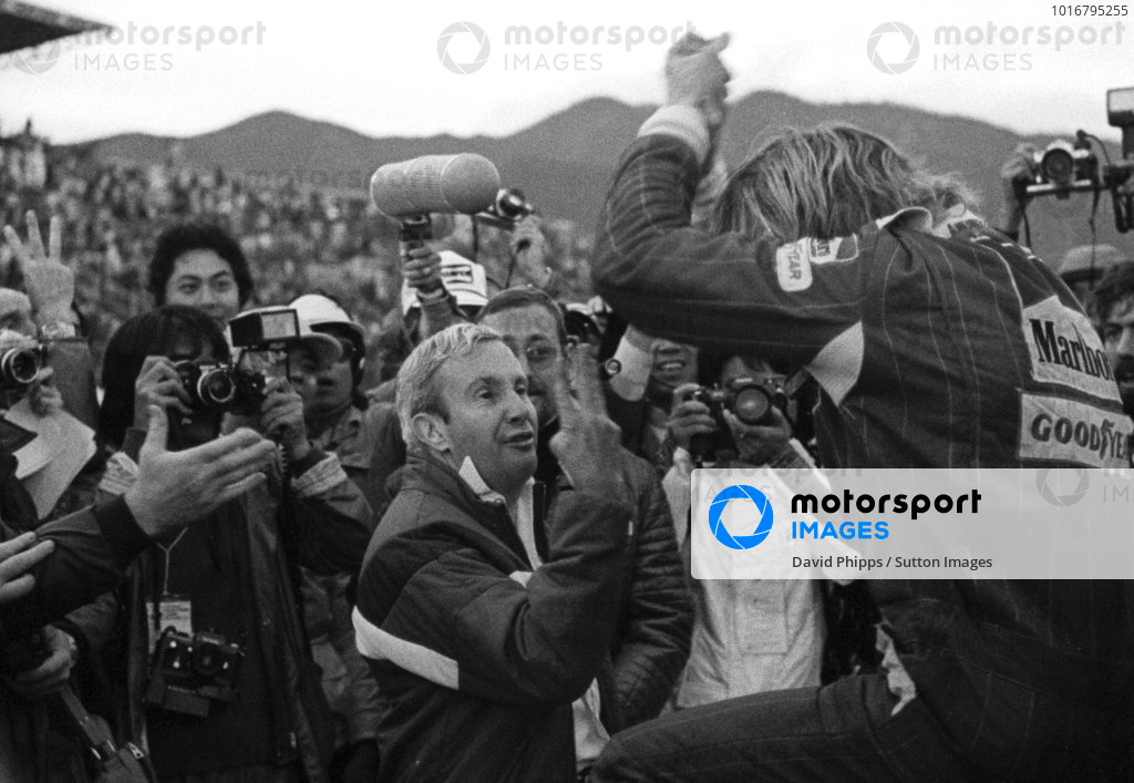 Teddy Mayer (USA), McLaren Team Manager, centre, holds three fingers up to James Hunt (GBR), climbing out of his McLaren immediately after the race, to signal that he had finished the race in third place and that he was now the 1976 Formula One World Champion. Hunt, who needed to finish fourth or higher to take the title, had climbed out of the car angry and unaware of his situation after a late race puncture had dropped him to fifth place.  Japanese Grand Prix, Rd16, Fuji, Japan, 24 October 1976.