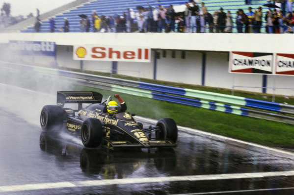 Ayrton Senna, Lotus 97T Renault, celebrates as he crosses the finish line and takes the chequered flag to secure his maiden F1 win.