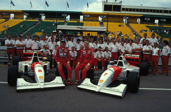 Ayrton Senna and Mika Häkkinen pose with their McLaren MP4-8 Fords and team personnel in the pitlane.