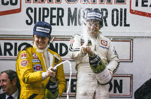 Mario Andretti celebrates victory on the podium with teammate Ronnie Peterson, 2nd position.