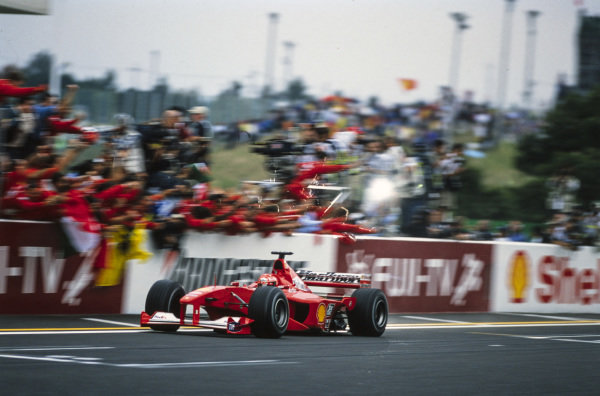 Michael Schumacher, Ferrari F1-2000, crosses the line for victory in the race and the drivers' world championship.