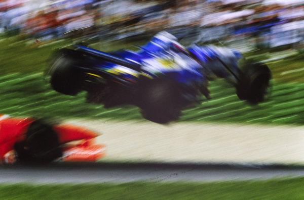 Jean Alesi, Benetton B197 Renault, flies through the air after a collision with Eddie Irvine, Ferrari F310B.