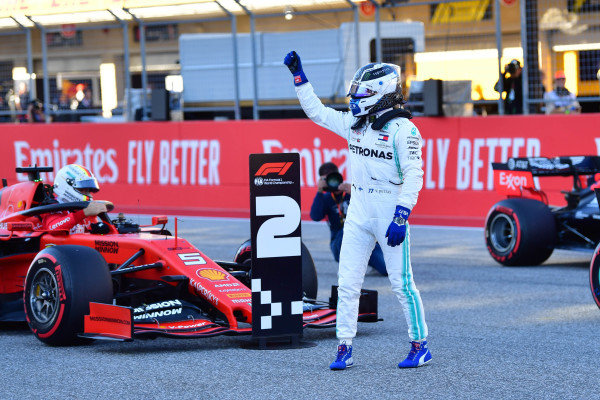 Valtteri Bottas, Mercedes AMG F1, celebrates after taking Pole Position as Sebastian Vettel, Ferrari, climbs from his car on the grid