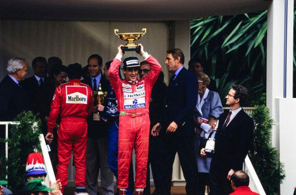Ayrton Senna celebrates on the podium.