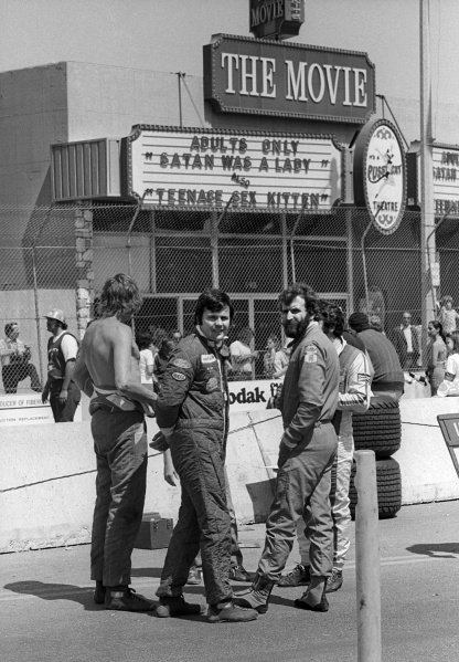 (L to R): James Hunt (GBR) McLaren; Alan Jones (AUS) Surtees; and Harald Ertl (AUT) take an interest in the adult cinema located opposite the pits, showing 'Satan Was A Lady' and 'Teenage Sex Kitten.'United States Grand Prix (West),  Rd3, Long Beach, USA, 28 March 1976.BEST IMAGE