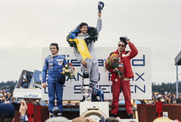 Jody Scheckter celebrates victory on the podium with teammate and Patrick Depailler, 2nd position, and Niki Lauda, 3rd position.