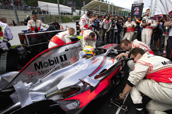 Mechanics work on Lewis Hamilton's McLaren MP4-22 Mercedes on the grid before the start.